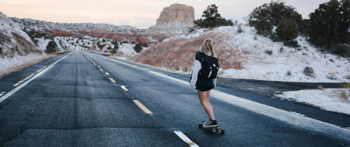 Jeune femme de dos faisant du skate sur une route