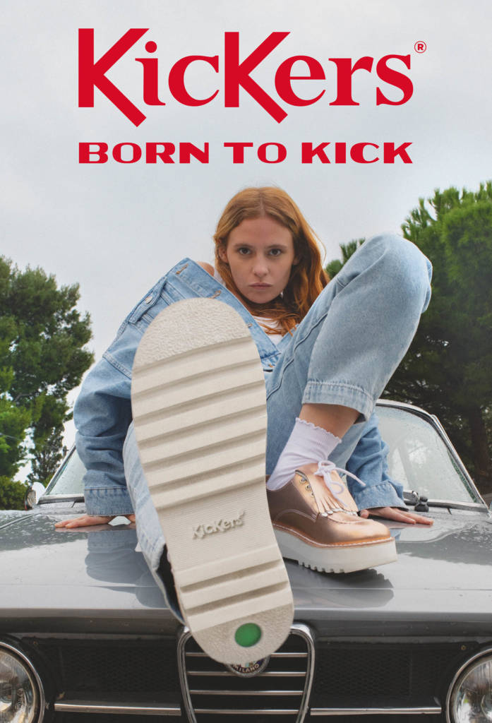 Flyer Kickers, avec une jeune femme sur le capot d'une voiture, montrant le dessous de sa chaussures, avec le logo Kickers