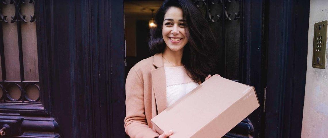 Jeune femme, devant la porte de son immeuble, tenant un colis dans ses mains