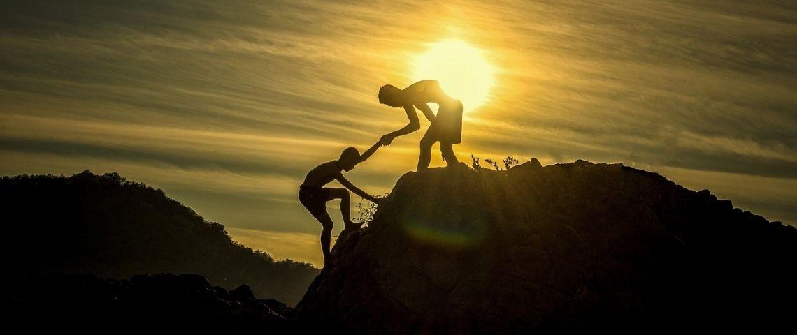 Homme aidant un autre homme à gravir une montagne