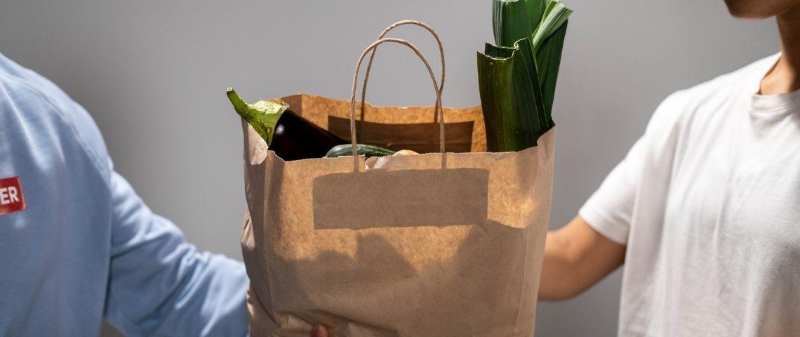 Personne donnant un sac de nourriture à une autre personne