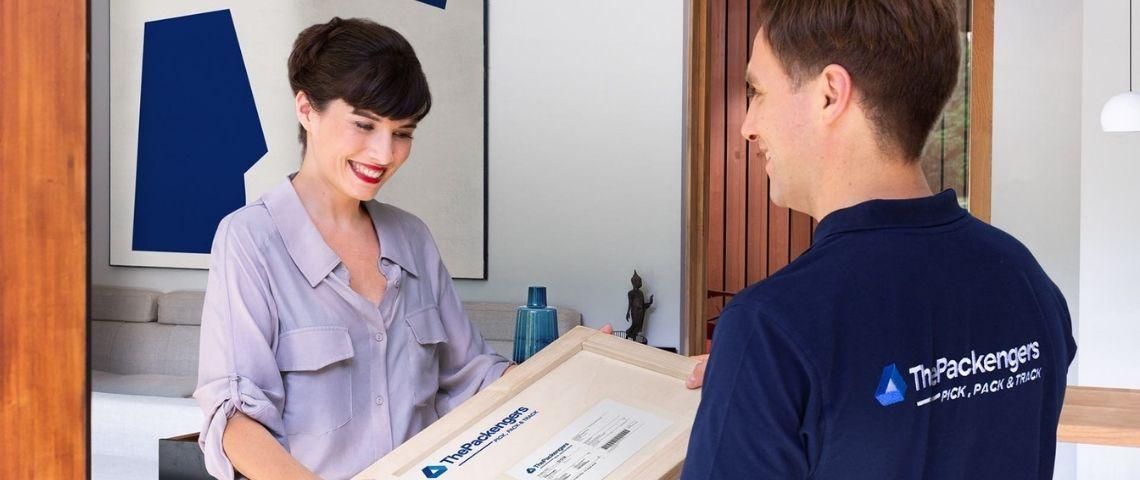 Femme recevant un colis, d'un livreur portant un t-shirt avec le le logo ThePackengers