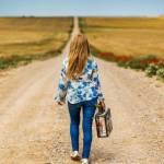 jeune fille marchant de dos sur un chemin à la campagne