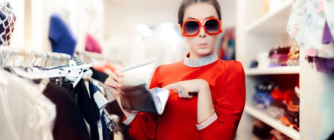 Une femme en train d'ouvrir son portefeuille dans une friperie