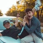 2 jeunes garcons alllongés sur le capot d'une voiture