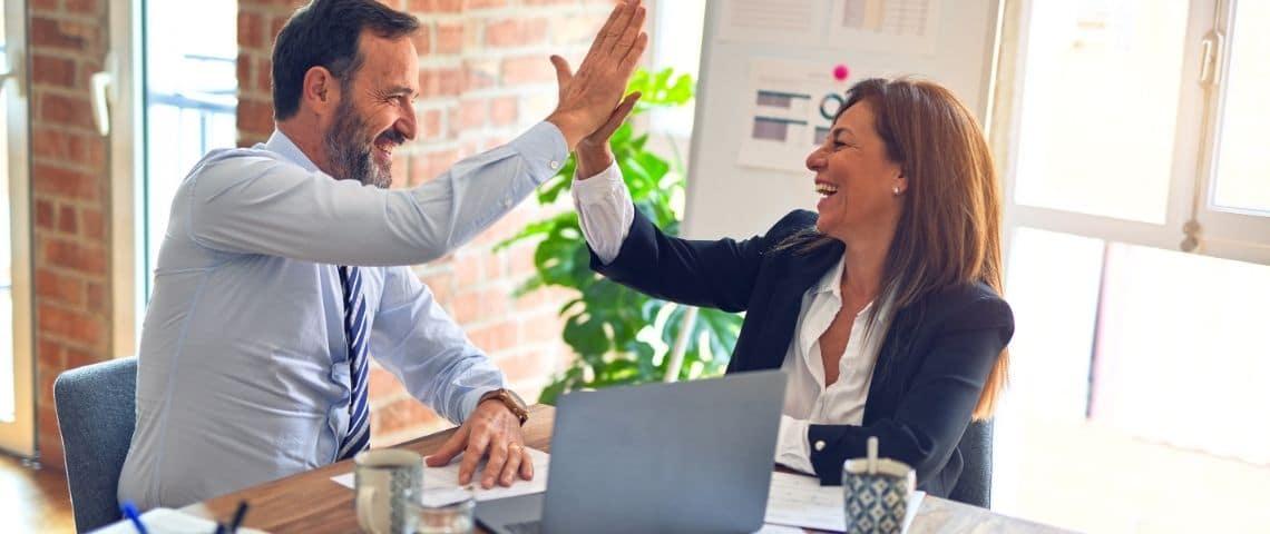 Une femme et un homme avec l'ai satisfait. Ils se tapent dans la main. Ils sont au bureau.