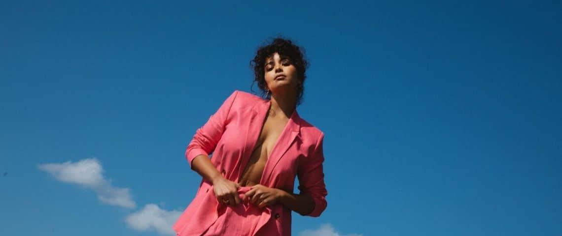 Une jeune femme en tailleur rose devant le ciel