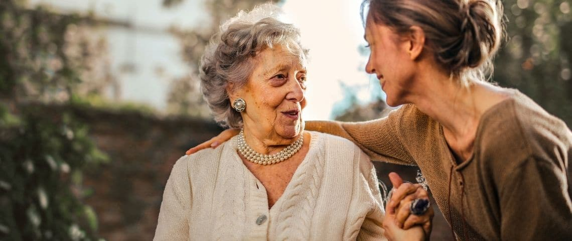 Une femme âgée et une femme adulte qui discutent avec l'air heureux