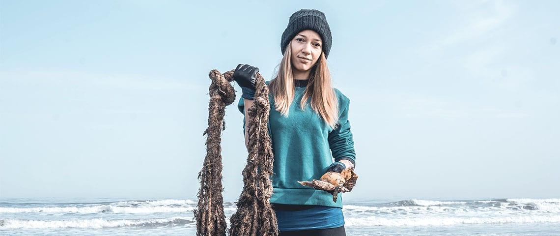 jeune fille qui sort des déchets de la mer