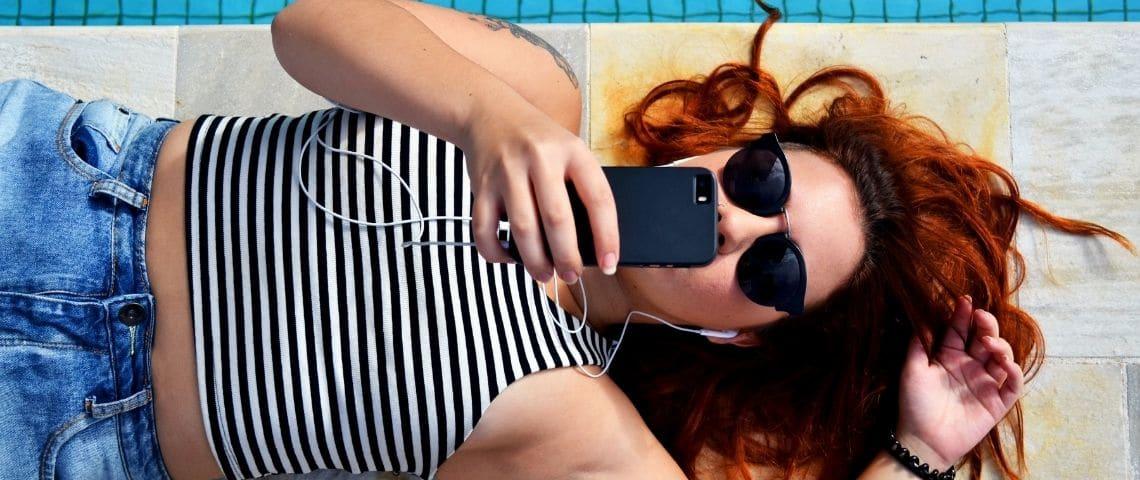 Jeune femme allongée au bord d'une piscine, elle regarde son téléphone