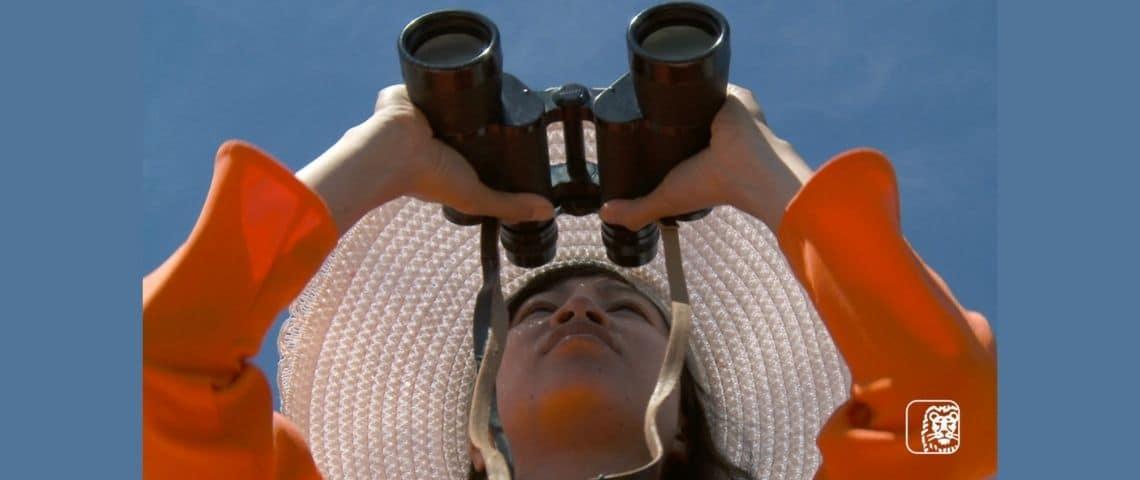 Une femme qui regarde au travers de jumelles