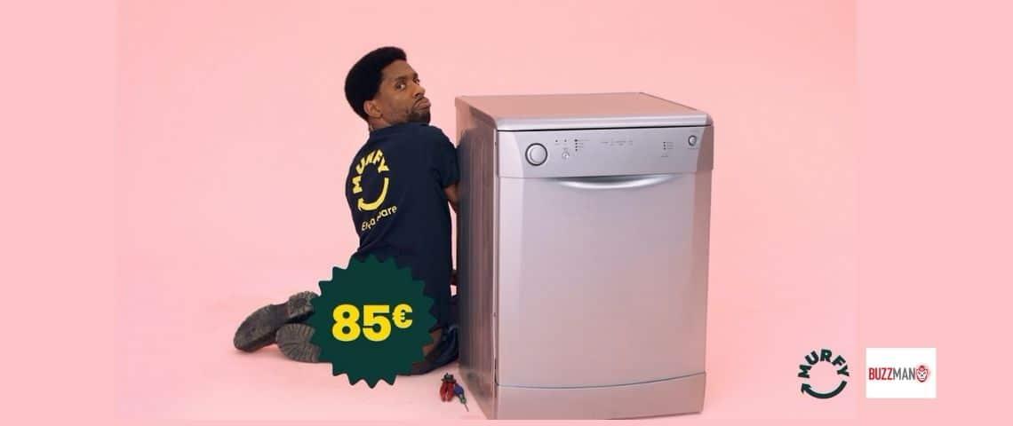Un homme à coté d'une machine à laver sur un fond rose