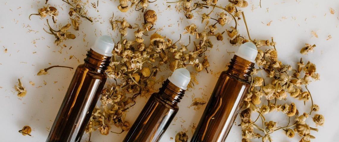 Plusieurs échantillons de parfum sur un lit de fleurs séchées