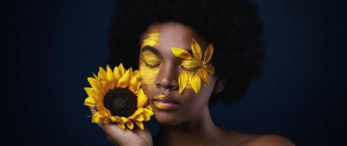 Une femme noire avec un tournesol et des pétales sur le visage