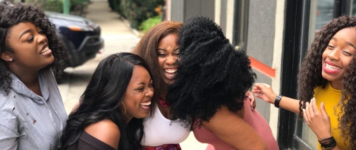Femmes noires se serrant dans les bras et riant