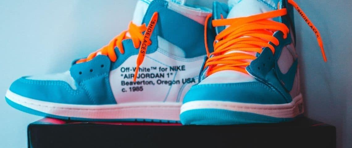 Une paire de baskets Nike bleue turquoise avec des lacets orange