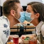 Deux adolescents qui s'embrassent avec des masques chirurgicaux