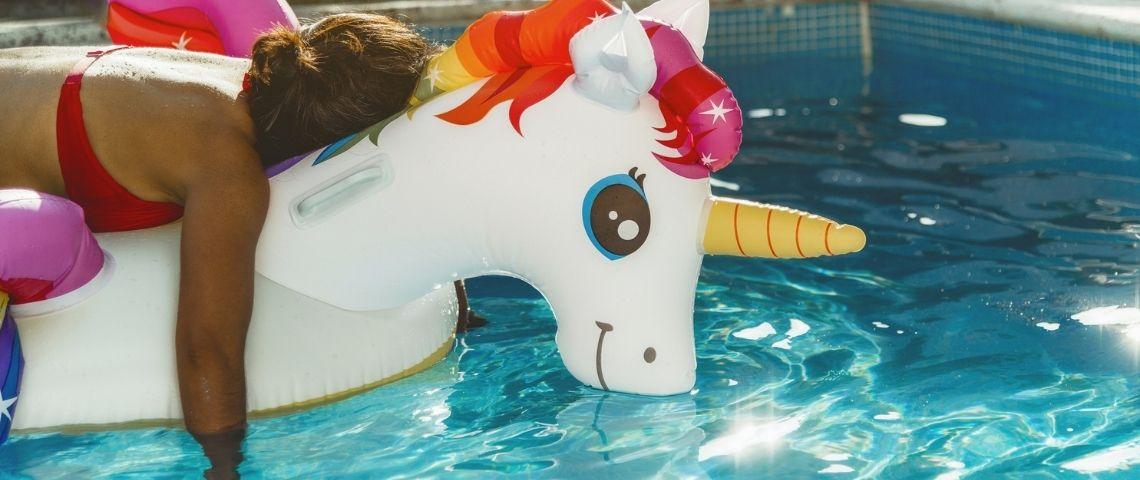 Une personne fatiguée sur une bouée licorne dans une piscine
