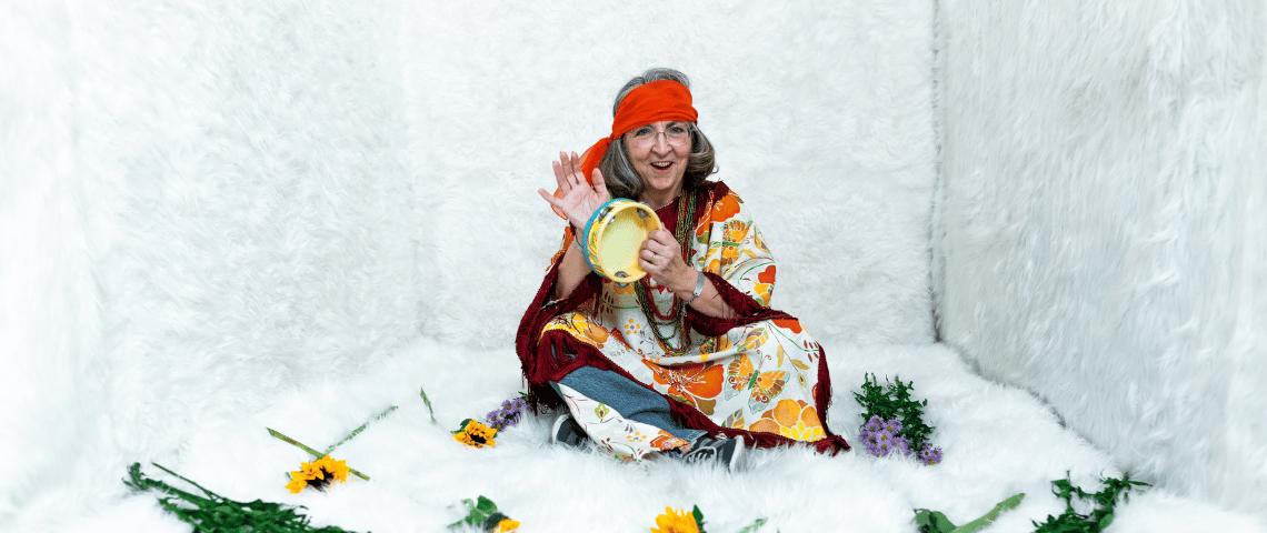 Une femme assise en tailleur habillée comme uen hippie joue du tambourin.