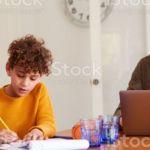 Papa travaillant sur son ordinateur pendant que la maman aide un enfant à faire ses devoirs