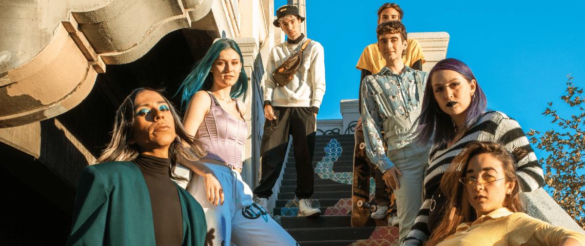 6 adolescents en tenues colores prennent la pose sur un escalier