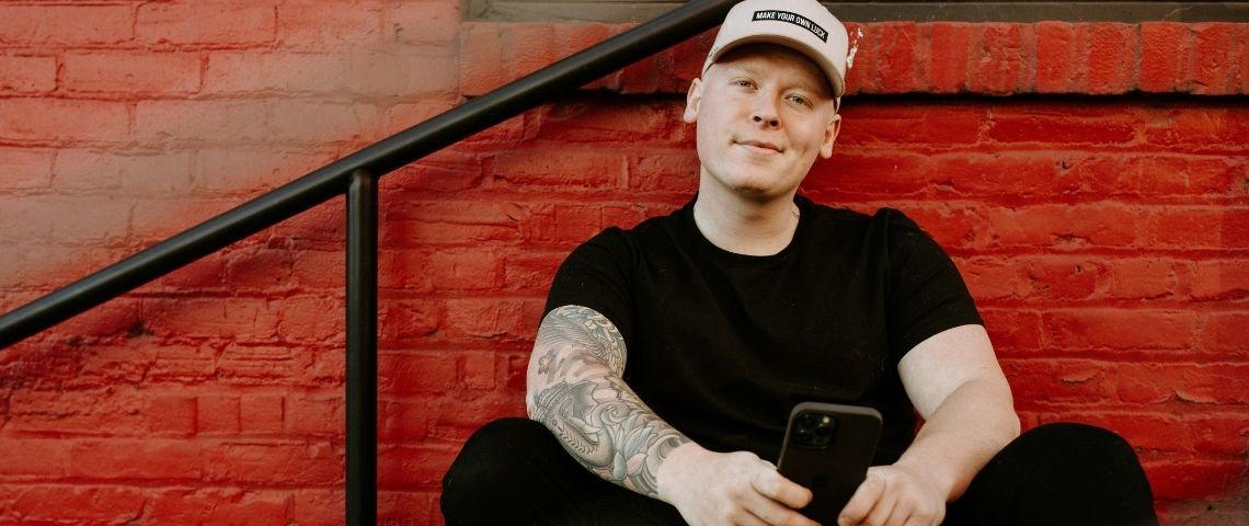 Un homme habillé en noir et tatoué sourit avec son smartphone