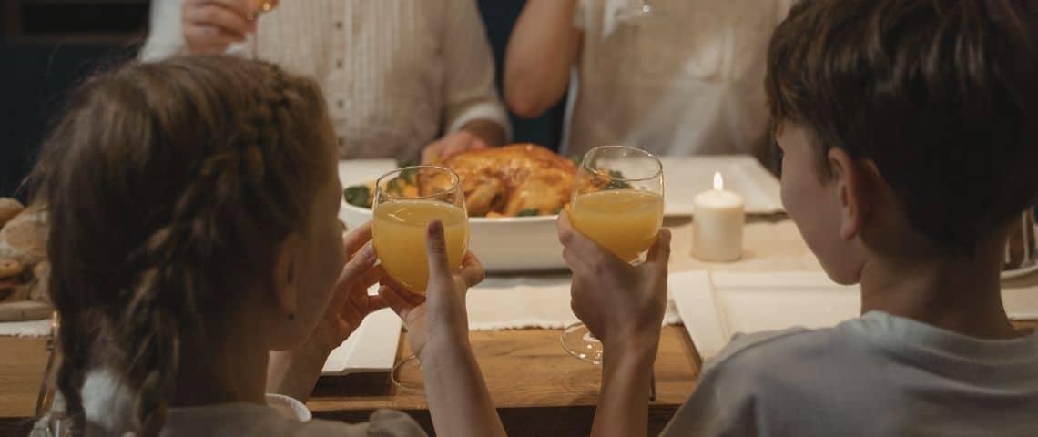 Deux enfants trinquant avec un verre de jus d'orange au restaurant