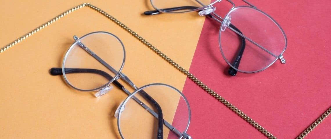 2 paires de lunettes sur fond orange et rose