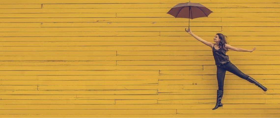 Jeune femme s'envolant en tanant un parapluie, sur un fond jaune