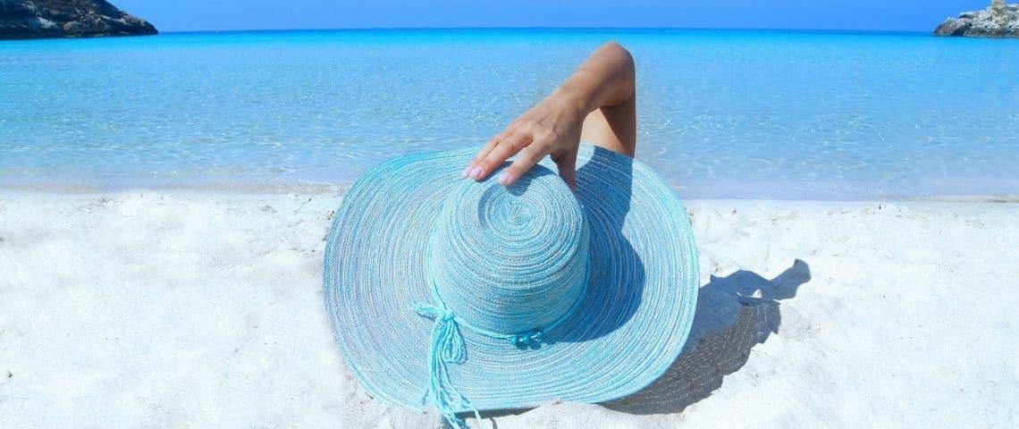 Femme allongée sur la plage, avec le visage caché derrière un chapeau de paille bleu