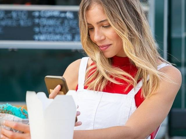 Une femme en train de prendre son sandwich en photo avec son smartphone