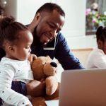 Un papa en train de s'occuper de ses deux petites filles en télétravail