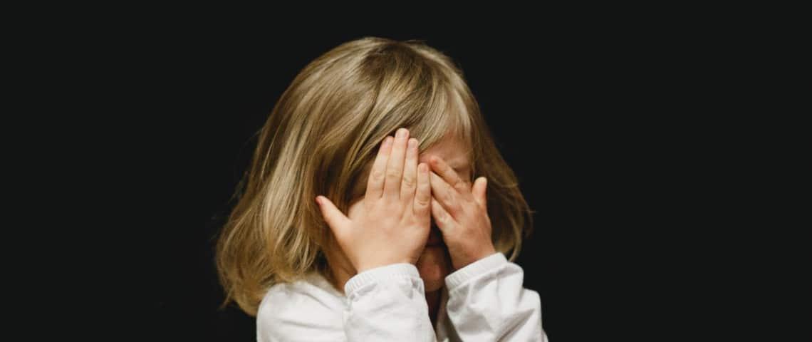 Une petite fille se cache le visage avec ses mains
