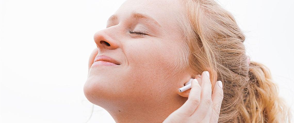 Jeune femme, les yeux fermés, sourir aux lèvres, la main sur son oreille dotée d'un écouteur