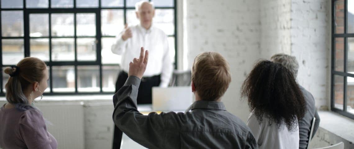 Cinq adultes dans une classe. Un lève la main