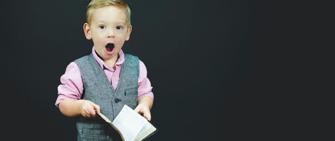 Un enfant déguisé en adulte, importe un costume et tient un livre dans sa main