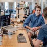 3 hommes qui discutent dans un bureau open space