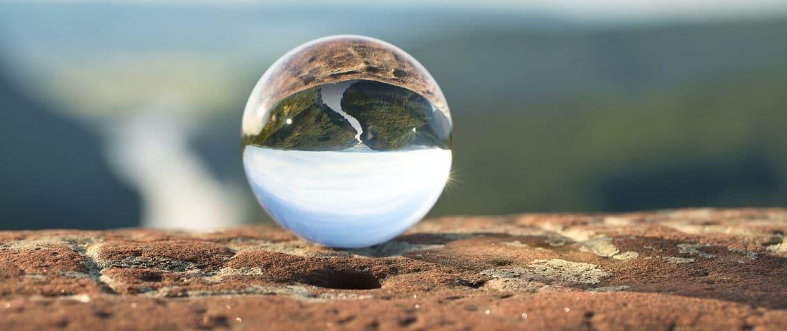 un paysage qui se reflète dans une boule en verre