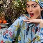 Une femme qui pose. Elle est habillée avec des vêtements a motifs