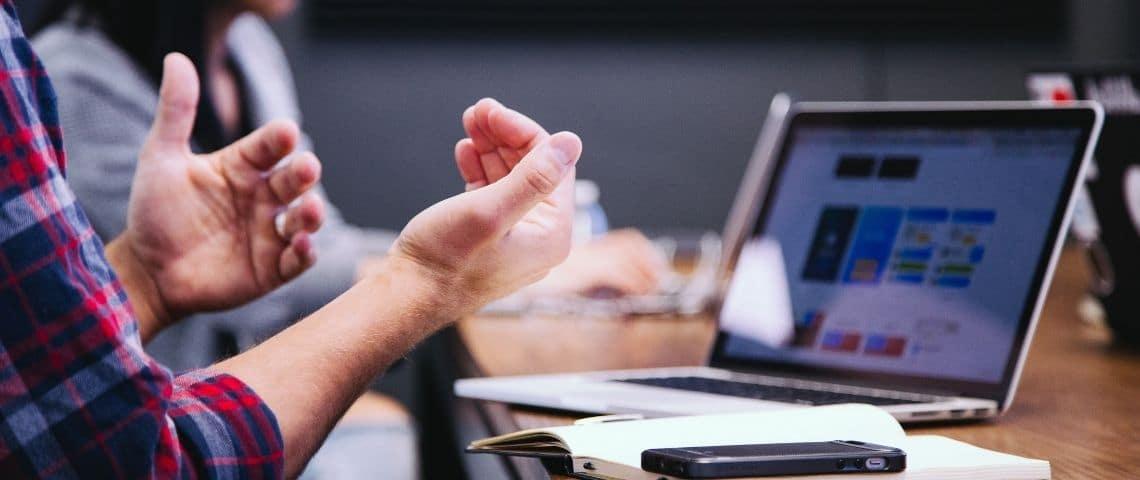 Des mains au premier plan. Un ordinateur au second