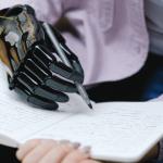 Homme avec une main bionique écrit sur un carnet au stylo