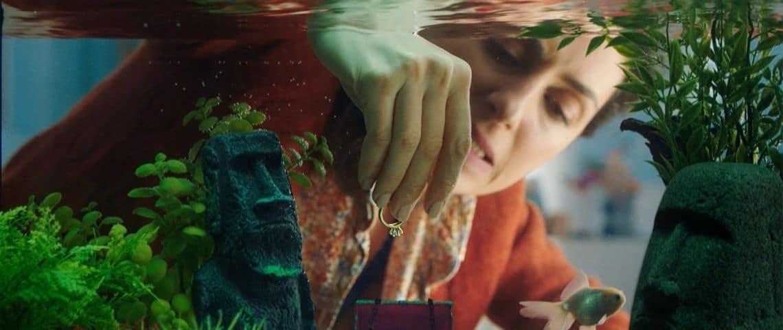 Femme mettant une bague dans un petit coffre fort dans un aquarium