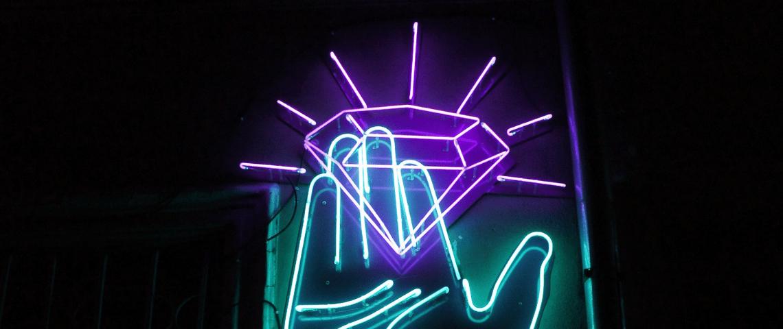 Une main bleue en néon tient un diamant violet aussi en néon