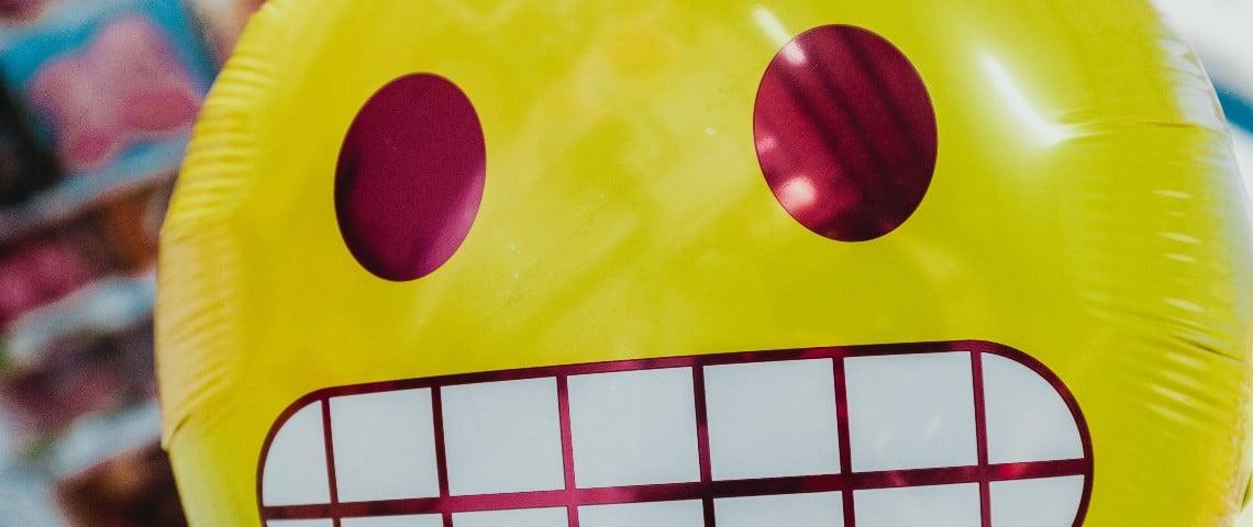 Un ballon de l'emoji qui grimace les dents serrés