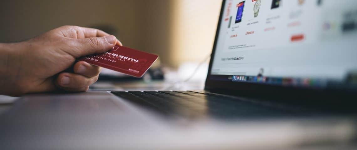 Personne tenant une carte bancaire devant un ordinateur