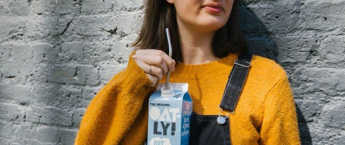 Une femme en salopette buvant une brique d'Oatly à la paille
