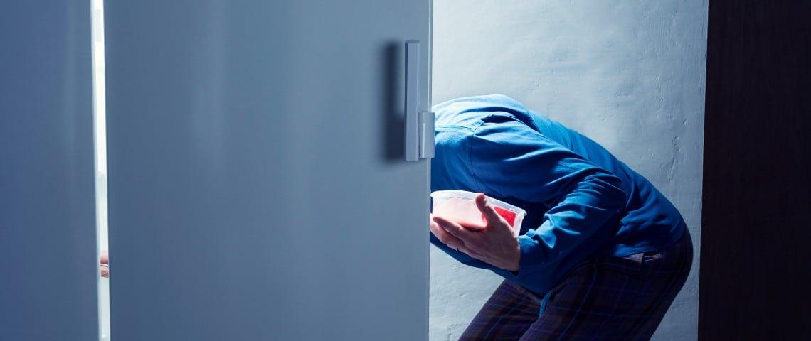Un homme se sert dans un frigo la nuit