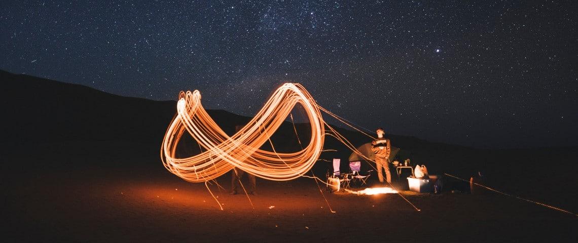 Un sigle infini dessiné en lumière par des personnes dans le désert
