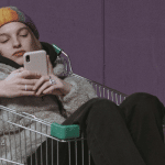 Une jeune femme assise dans un chariot tient son téléphone portable