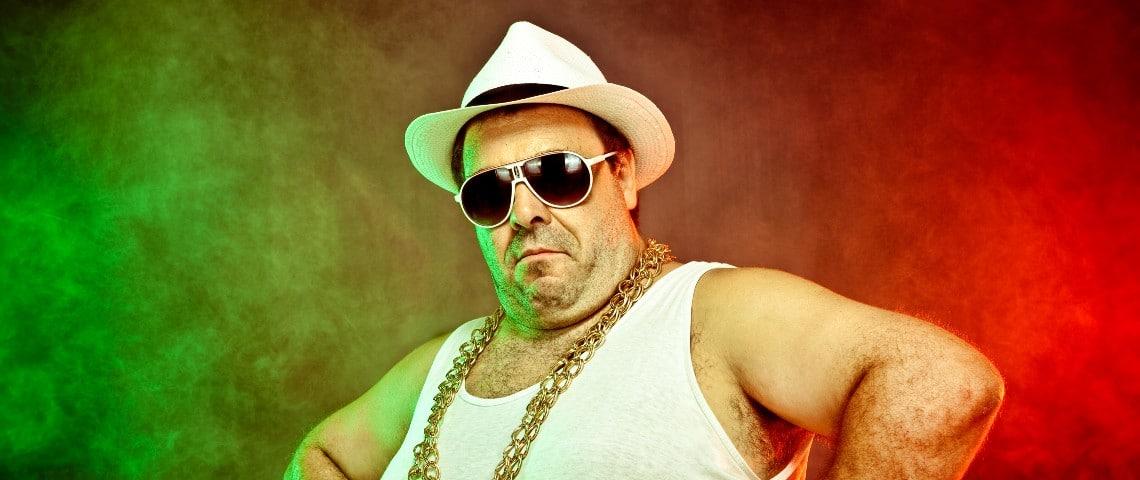 Un monsieur en marcel porte une grosse chaîne et un chapeau